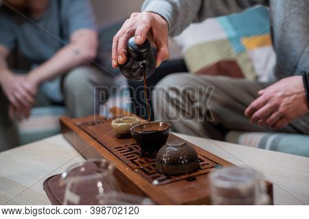 Mens Hands Pour Fragrant Amber Tea Into A Glass Bowl. Tea Ceremony And Tasting In Traditional Chines