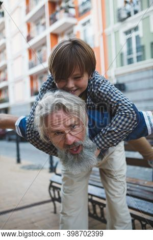 Vertical Shot Of A Cute Young Boy Having Fun With Grandpa, Piggyback Riding On City Streets