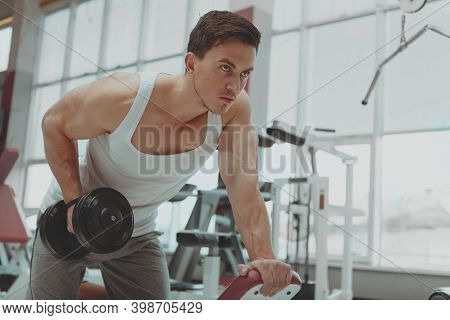 Low Angle Shot Of A Handsome Muscular Male Athlete Doing Triceps Exercise At The Gym Lifting Dumbbel