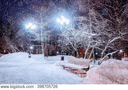 Christmas background. Winter Christmas night landscape - snowy bench under frosty winter trees and shining lights. Winter Christmas night landscape with winter falling snowflakes