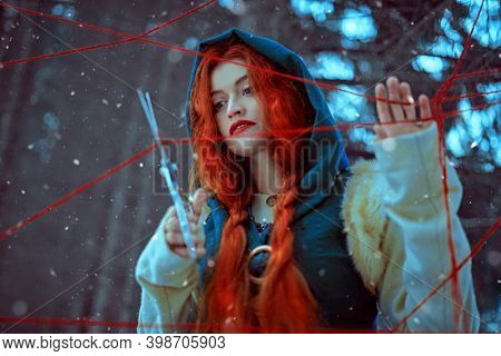 The medieval sorceress cuts the threads of fate in the thicket of the winter forest. Historical reconstruction of the Middle Ages. Fairy tales.