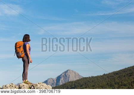 A Woman With A Backpack Stands On Top Of A Mountain And Admires The Beauty Of A Mountain Valley, The