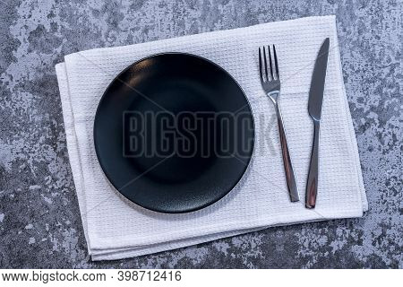 Black Plate, Cutlery With Utensils And Napkin On Rustic Stone Table Top View. Table Setting.