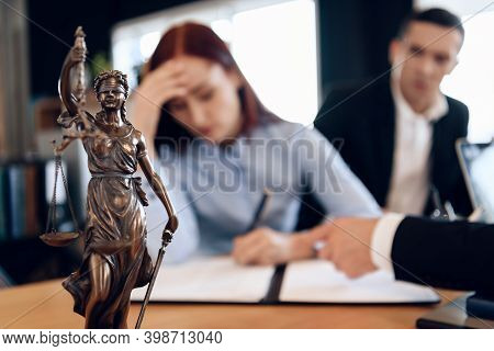 Bronze Statue Of Themis Holds Scales Of Justice. In Unfocused Background, Couple Signs Documents.