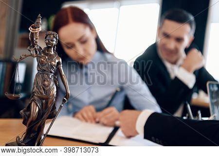Bronze Statue Of Themis Holds Scales Of Justice. In Unfocused Background, Adult Signs Documents.