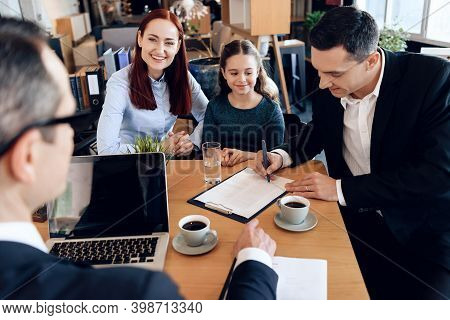 Adult Father, Red Head Mother And Little Smiling Daughter Are Sitting In Lawyer Office. The Family C