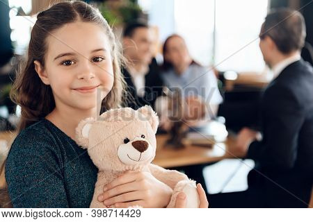 Happy Little Girl Is Hugging Teddy Bear At Office Of Family Lawyer. Registration Of Guardianship.