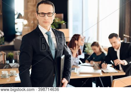 Serious Adult Man In Glasses Stands In Front Of Office Of Family Lawyer.