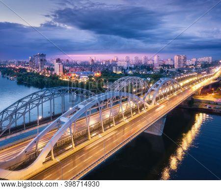 Aerial View Of Beautiful Bridge At Night In Kiev, Ukraine. Landscape With Bridge, River, City Illumi