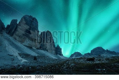 Aurora Borealis Over The Mountains At Night In Europe. Northern Lights. Starry Sky With Polar Lights