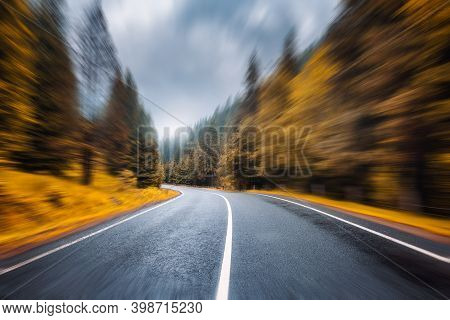 Road In Autumn Foggy Forest In Rainy Day With Motion Blur Effect. Beautiful Mountain Roadway And Blu
