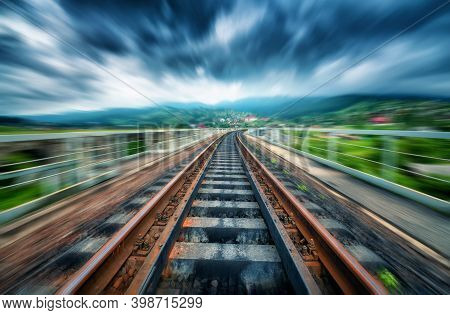 Railroad Bridge In Mountains In Overcast Day With Motion Blur Effect. Railway Station And Blurred Ba