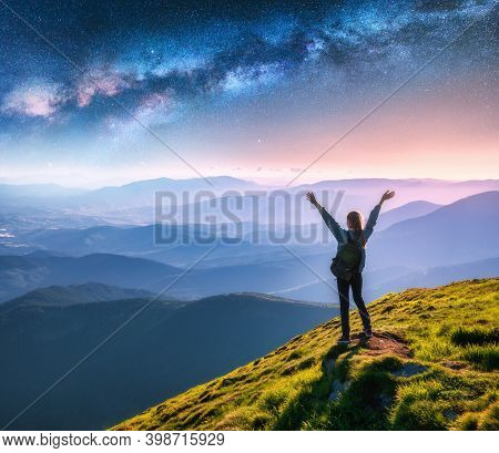 Happy Young Woman On The Mountain Peak And Arched Milky Way Over Mountains At Night. Landscape With