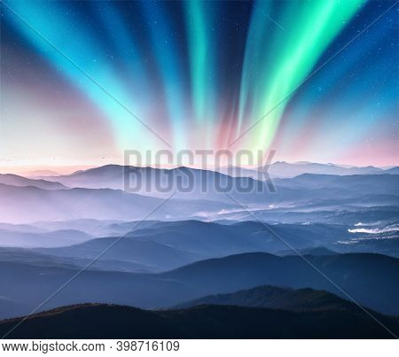 Aurora Borealis Above The Mountain Valley In Low Clouds At Night. Northern Lights In Winter. Night L