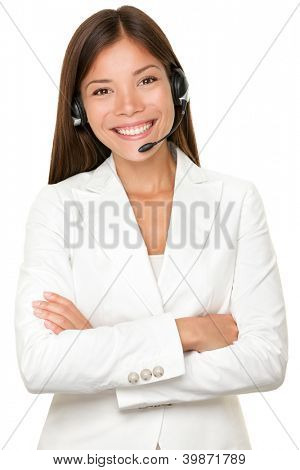 Beautiful cheerful young Asian call operator, receptionist or personal assistant wearing a headset and microphone standing with her arms folded isolated on white