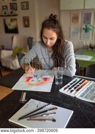 Woman At Home At The Table, Draws Paints, Portrait Of A Girl. Bright Orange Paints, Color Palette. B