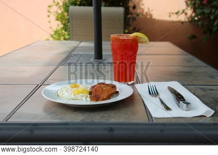 Breakfast or Brunch. Eggs and Pork Chop with Bloody Mary. Outdoor dining breakfast. Brunch with Bloody Mary and Pork Chop with Eggs Easy Over.