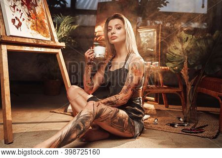 Posing In Dark And Atmospheric Studio Room Beautiful Tattooed And Grimy Woman Holding Coffee Cup And