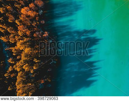 Top Down View From Above Of A Serene Turquoise Mountain Lake And A Boreal Forest In Autumn Colors.