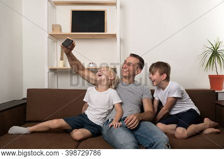 Young Father And Two Sons Take Pictures Of Themselves On Smartphone On The Couch At Home