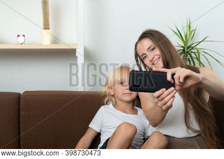 Mom And Son Take Selfie Sitting On A Couch. Young Woman And Boy Take Photo On A Smartphone