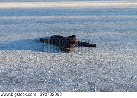 A Boy In Skates Slipped And Fell On The Ice On The River In Winter.