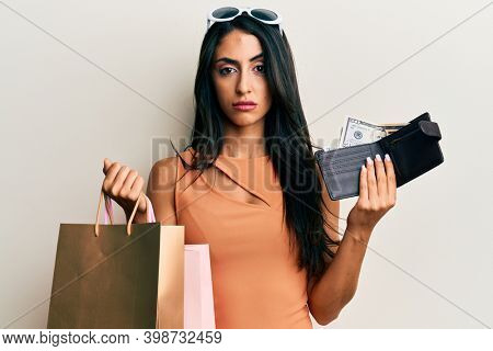 Beautiful hispanic woman holding shopping bags and wallet with dollars skeptic and nervous, frowning upset because of problem. negative person.