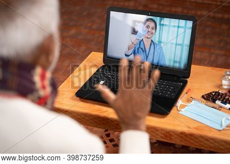 Shoulder Shot Of Old Man On Video With To Doctor On Laptop Screen - Concept Of Online Chat, Teleheal