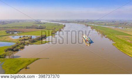Inland Container Ship On River Lek Aerial View Near The Village Of Ravenswaaij, Gelderland, Netherla