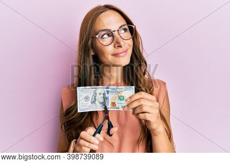 Young brunette woman cutting dollars with scissors for currency devaluation smiling looking to the side and staring away thinking.