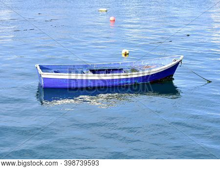 Old Blue And White Wooden Small Fishing Boat Floating On The Sea At Famous Rias Baixas In Galicia Re