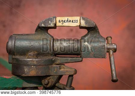 Concept Of Dealing With Problem. Vice Grip Tool Squeezing A Plank With The Word Agedness