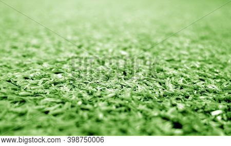 Green Color Artificial Grass Close-up With Blur Background. Texture And Backdrop