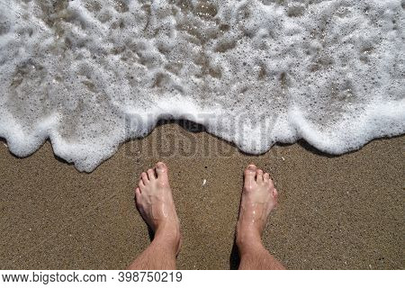 Man's Feet From Top And Sea Wave And Sand. Travel Scene And Background