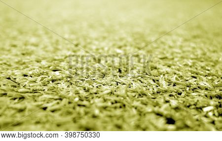 Yellow Color Artificial Grass Close-up With Blur Background. Texture And Backdrop
