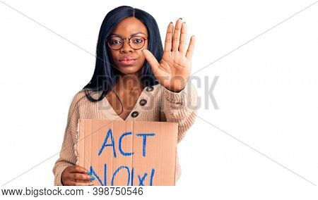 Young african american woman holding act now banner with open hand doing stop sign with serious and confident expression, defense gesture
