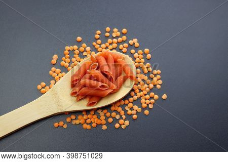 Red Penne Paste In A Wooden Spoon And Scattered Red Lentils On A Gray Background. Red Lentil Penne P