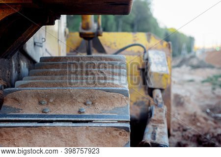 Bulldozer Stands On The Sand Near The Forest. Close-up Of A Metal Track Of A Bulldozer. Laying A New