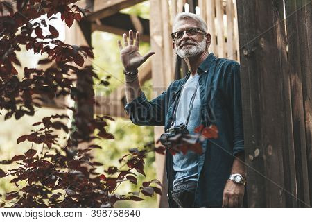 Retired Neighbor With A Beard Greets And Smiles On The Terrace Of The House. Support And Care For Ol