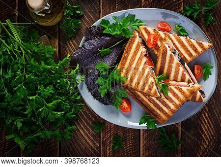 Grilled Club Sandwich Panini With Ham, Tomato, Cheese And Leaf Mustard. Delicious Breakfast Or Snack