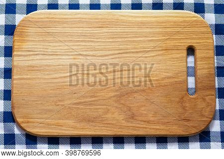 Close Up Of Wooden Cutting Board On Checkered Tablecloth Napkin
