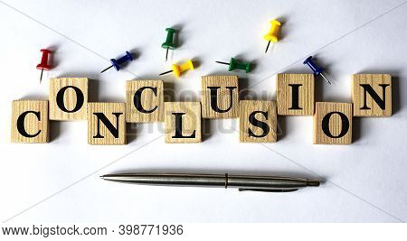 Conclusion - Word On Wooden Cubes With Stationery Buttons, Pen On White Background. Info Concept