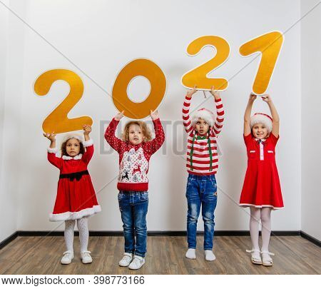 Four Funny Little Girls In Santa\'s Helper Costumes Stand With Big New Year Numbers On A White Backg