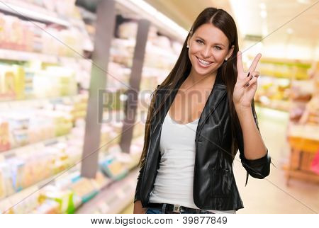 Young Woman Giving Victory Sign at a supermarket