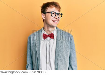 Young caucasian nerd man wearing glasses wearing hipster elegant look with bowtie looking away to side with smile on face, natural expression. laughing confident.