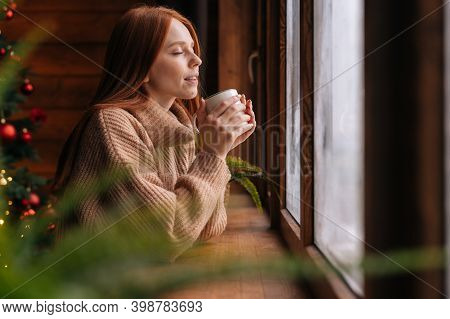 Charming Happy Young Woman Looking Out Of Window And Drinking With Enjoying Hot Coffee At Home At Ch