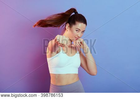 Attractive Female Boxer Wearing White Tank Top Posing In Boxing Pose, Looks At Camera, Training Her