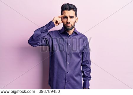 Young handsome man with beard wearing casual shirt pointing unhappy to pimple on forehead, ugly infection of blackhead. acne and skin problem