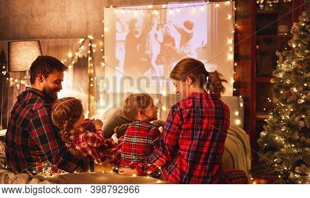 Happy Family In Checkered Pajamas: Mother Father And Children Watching Projector, Film, Movies With