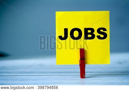 Reminder Sticky Note With Clothes Pin On Table. Sticky Note With Word Jobs. Search Job Concept